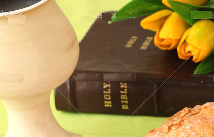Chalice with red wine, bread, Holy Bible and tulips